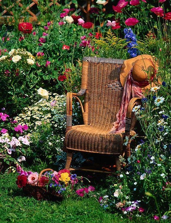 Antique Wicker Rocking Chair In A Flower Garden Pictures